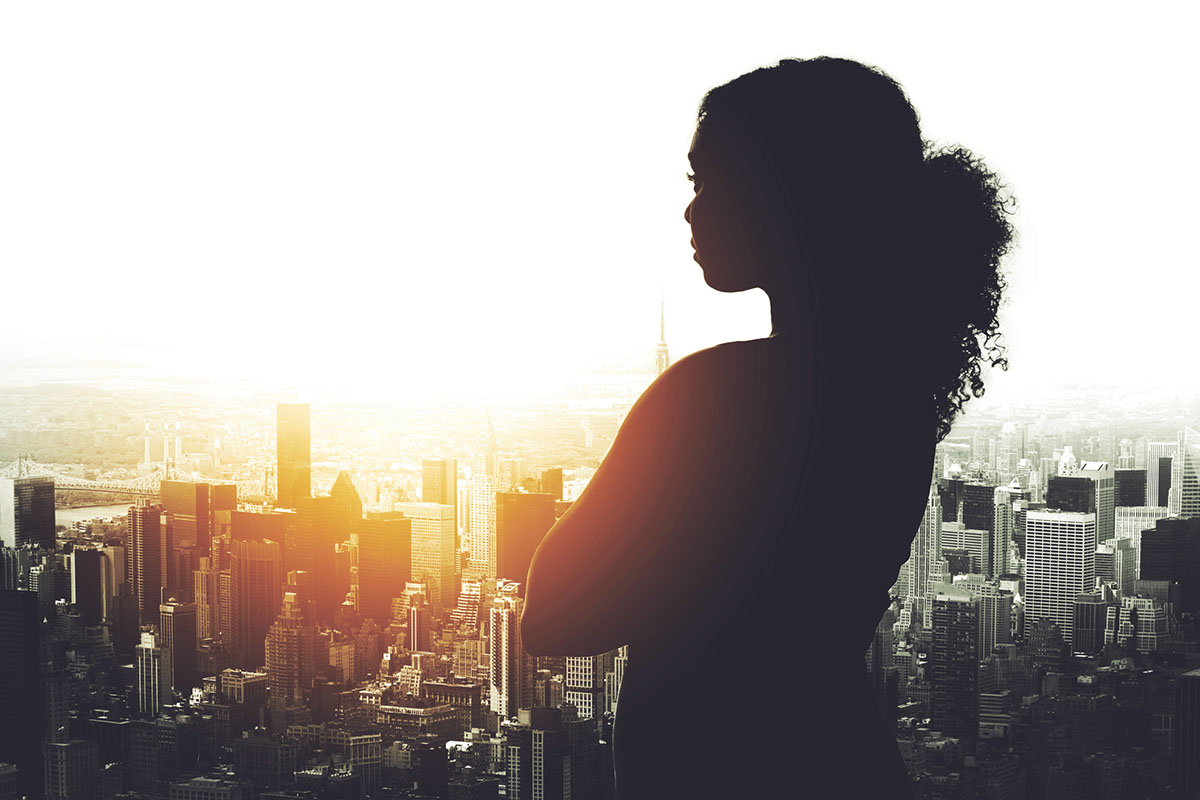 Silhouetted shot of a young HR professional looking at a cityscape from an office window