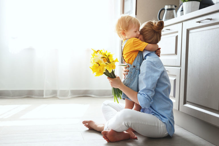 Businesswomen sited in bright kitchen while baby son gives her flowers