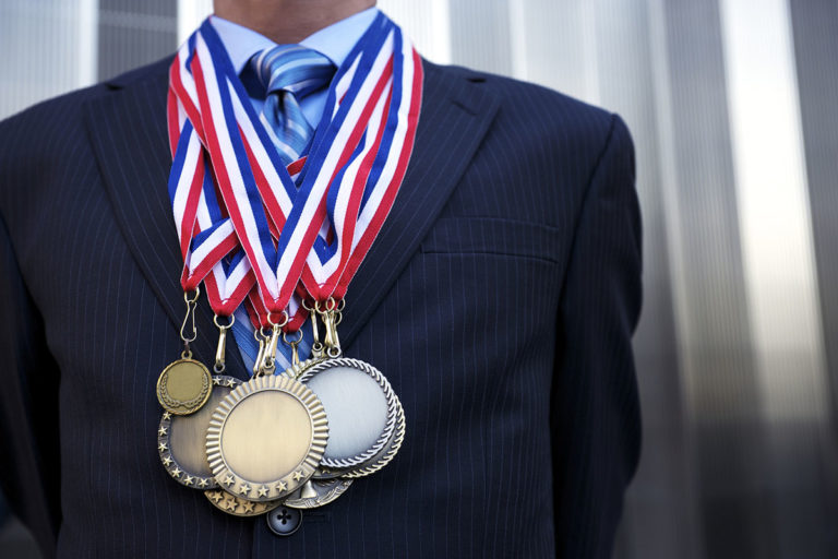 Businessman Standing Outdoors Decorated with Olympic Medals