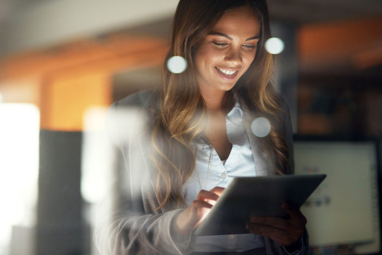 Businesswomen reading HR analytics article on tablet