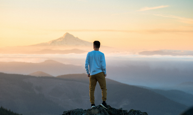 An HR professional standing in front of a mountain peak at sunrise contemplating the three mistakes to avoid when starting an analytics function