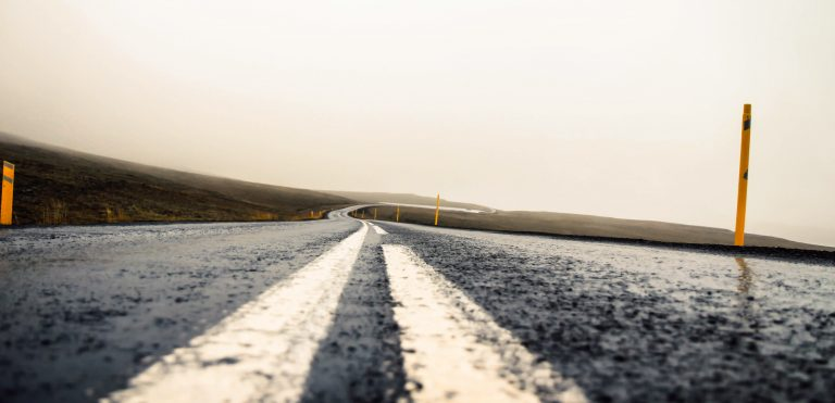 A picture of a wet road winding off into the distance with two median lines separating each side of the road