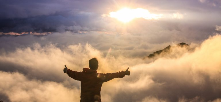 A man standing on the top of a peak with his thumbs up and overlooking a cloud-filled vista with the sun peeking out from the clouds above him