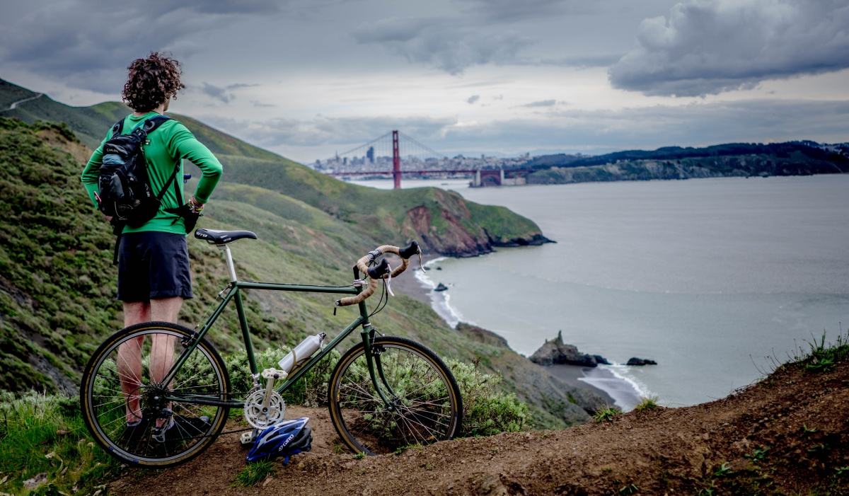 A People Analytics leader is contemplating how to advance people analytics while standing on the side of a hill looking out at San Francisco Bay and the Golden Gate bridge. He has just cycled there and his bike is beside him.