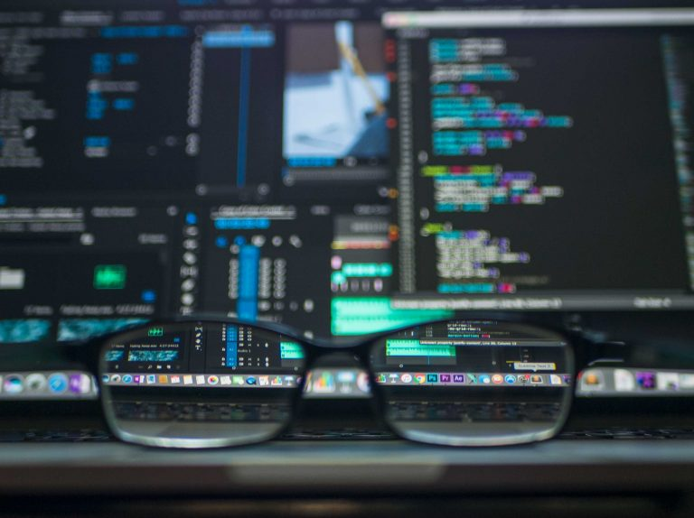 An HR professional's glasses sitting on top of their computer as they look at HR data and the talent data trends for 2018