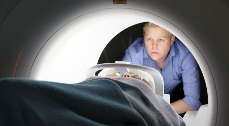 A nurse looks into an MRI machine where a patient is lying