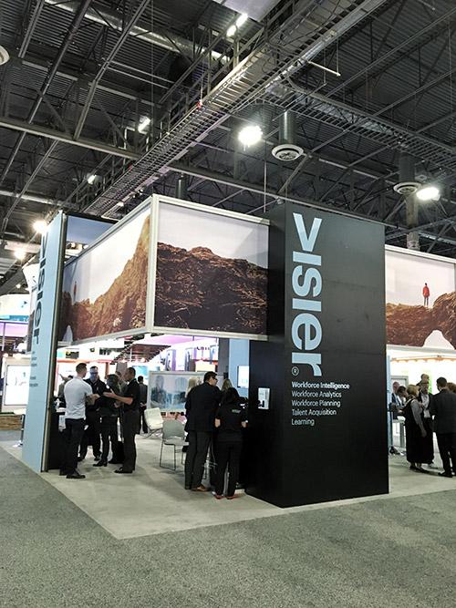 The Visier booth as seen at HR Technology Conference. It features black and clarity blue panels with the Visier logo and product offerings: Workforce analytics, workforce planning, talent acquisition and learning