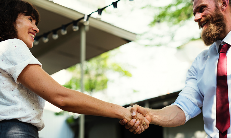 A female HR professional and male HR professional are shaking hands because they're using the agile method to take action on employee feedback