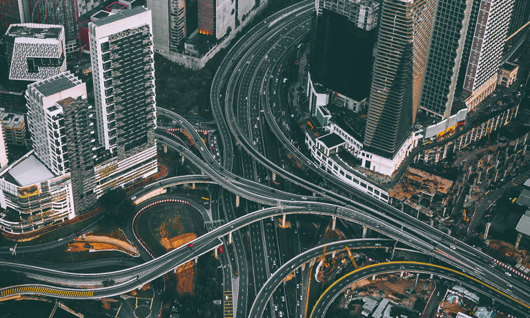 A sweeping interconnected highway that weaves between tall buildings in a city acts as a metaphor for using organizational network analysis to uncover teh hidden collaborative networks within a company