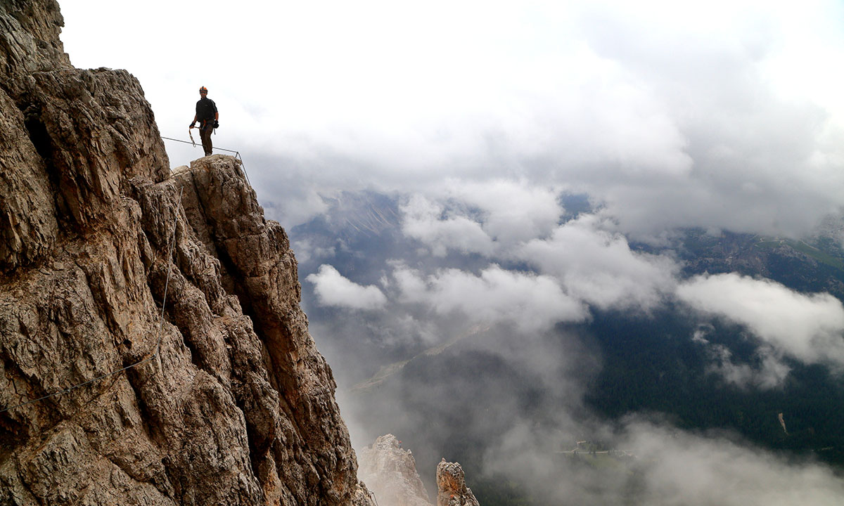 An HR executive standing on top of a cliff with clouds below and an uncertain path ahead. This image is a metaphor for why HR must use people analytics to make strategic directions.