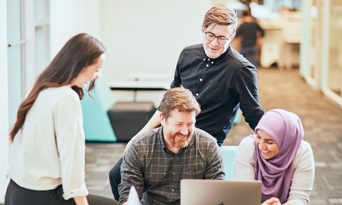 A group of HR technologists gathered around a computer as they discuss the skills they need to develop in the next eight years to succeed in the new world of work
