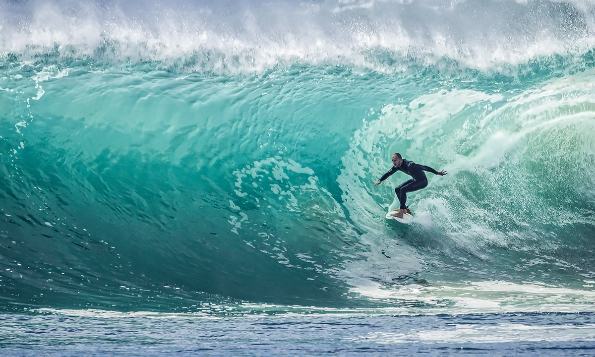 A surfer riding a wave in the summer as a metaphor for keeping learning flowing with top people analytics articles for summer 2018