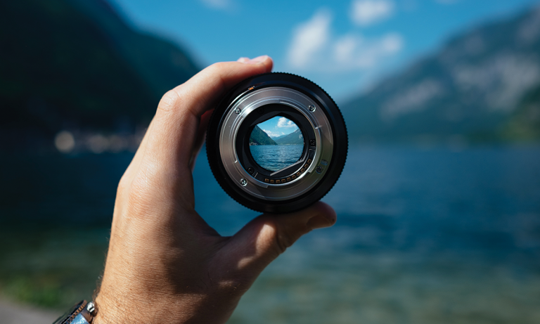A hand holds up a lens to a view of a lake between mountains. It's a metaphor for using a data-driven method for identifying toxic employees.
