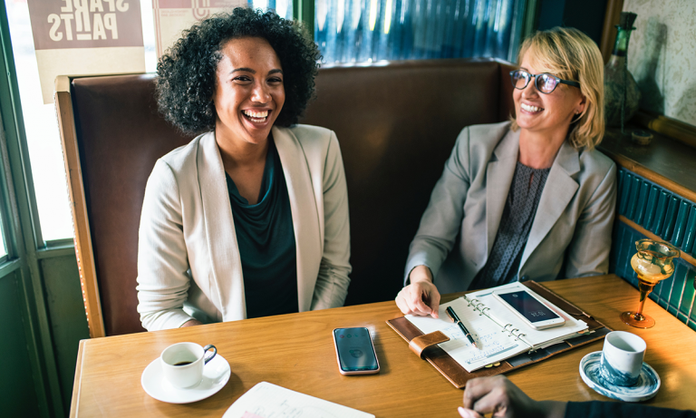 Two female HR executives discussing how to tackle the gender wage gap in Canada