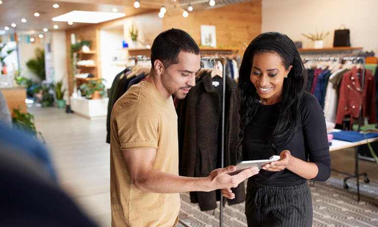 A clothing retail store worker holding a tablet helps a customer. There are clothes hanging in racks behind them. This photo is a metaphor for retail HR using people analytics to avoid holiday retail worker shortfalls.