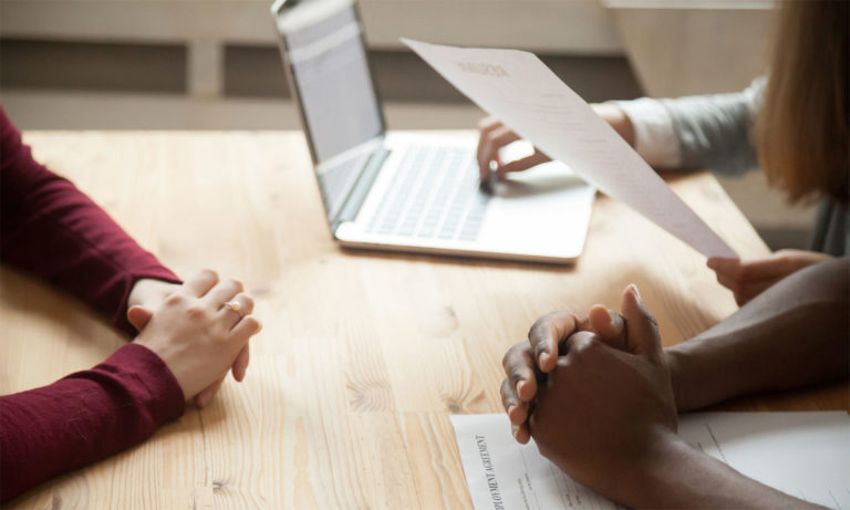 "Three pairs of hands are resting on top of a wooden table. One person has their hands on a laptop and holds a sheet of paper with the words ""resume"" on it. Another person has an employer agreement contract in front of them. The third person sits across from the other two with their hands folded."