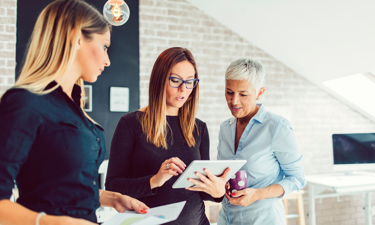 Three female HR executives looking over the difference between reports and analytics