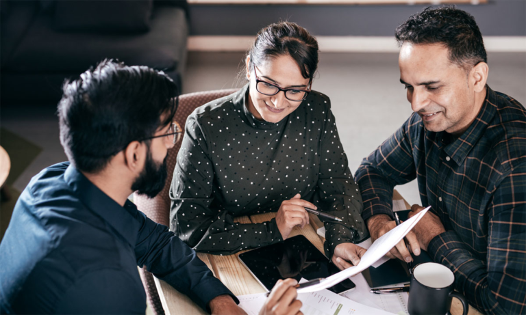 Two men and one woman looking over a report together as a metaphor for three ways hr professionals can use people data in the employee lifecycle