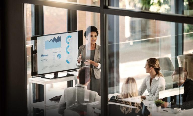 Female HR leader delivering a data visualization rich presentation to her senior executives