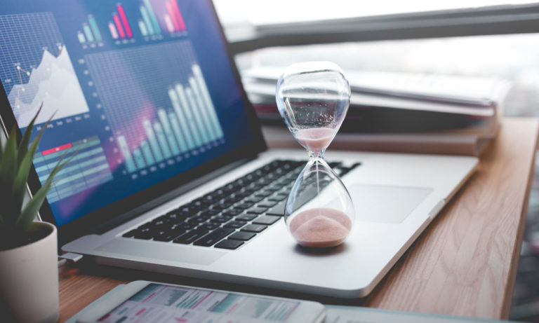 A sand timer shows people analytics data visualizations in the background as a metaphor for the time to value of different people analytics solutions