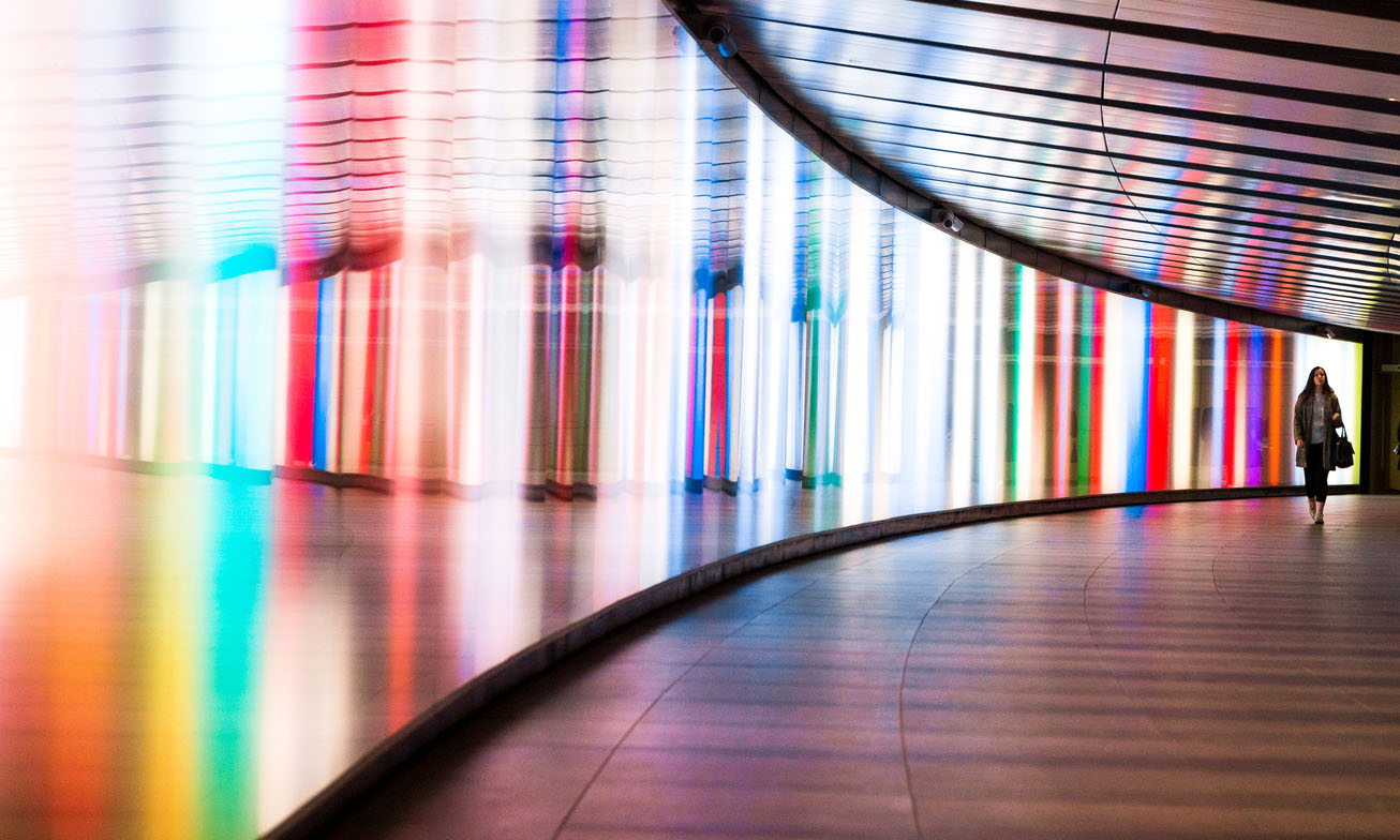 Wide angle color image depicting the front view of a young HR executive walking through a futuristic subway tunnel in central London, UK. The tunnel is illuminated with multi colored lights. The woman is in the far distance, and the focus is on the cool science fiction architecture of the subway tunnel that curves round into the distance.