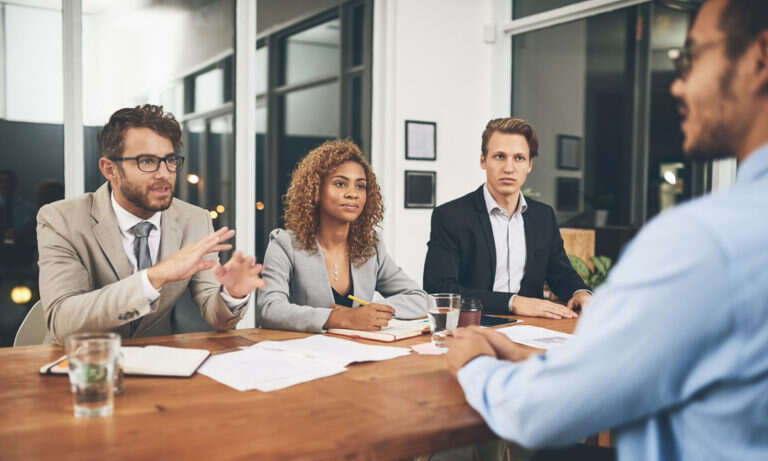 Shot of a group of businesspeople interviewing a candidate in an office because they used a people analytics solution with their HRMS data to improve recruitment
