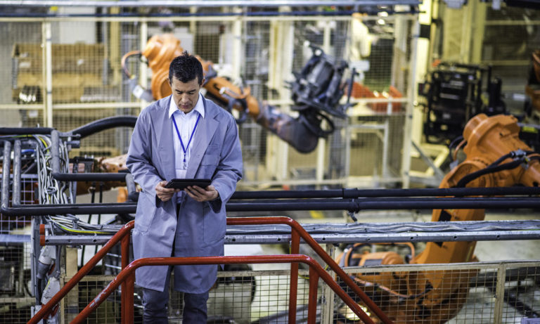 A business leader looking down at his tablet as he stands in a factory surrounded by machines as a metaphor for work automation