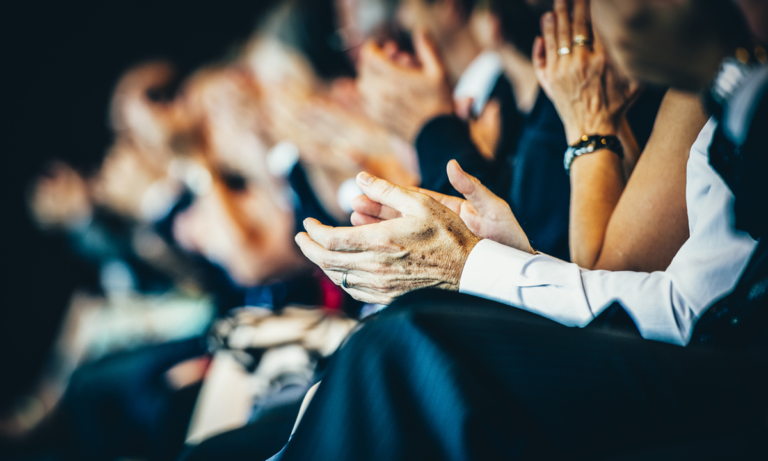An audience of HR leaders clapping their hands at an event