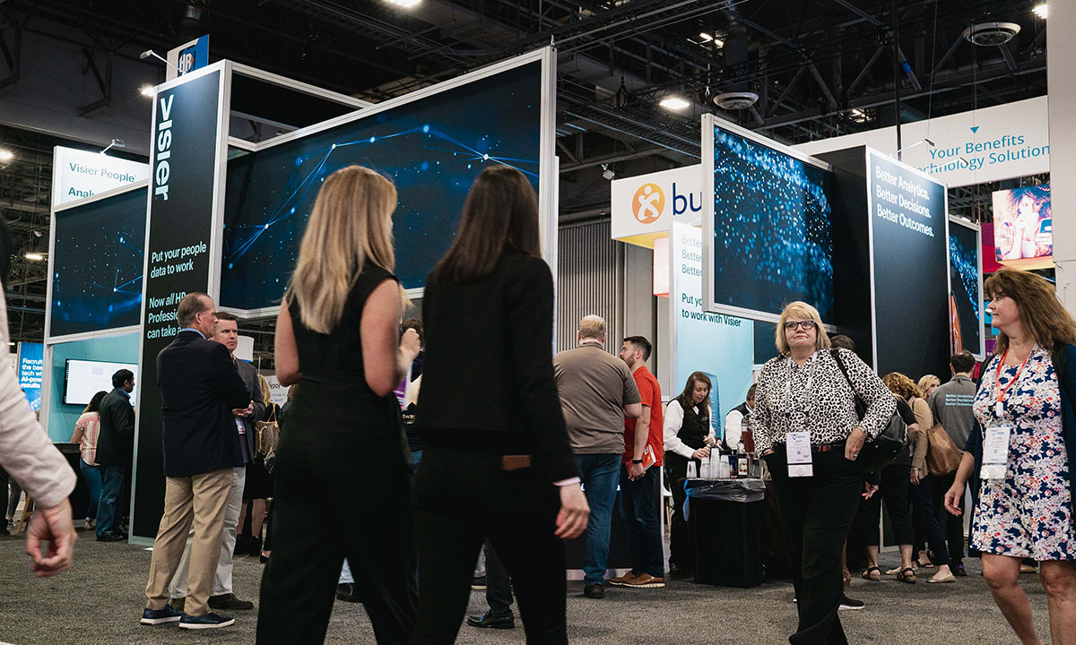 HR Technology Conference 2019 attendees in the Visier booth and walking in front of the booth