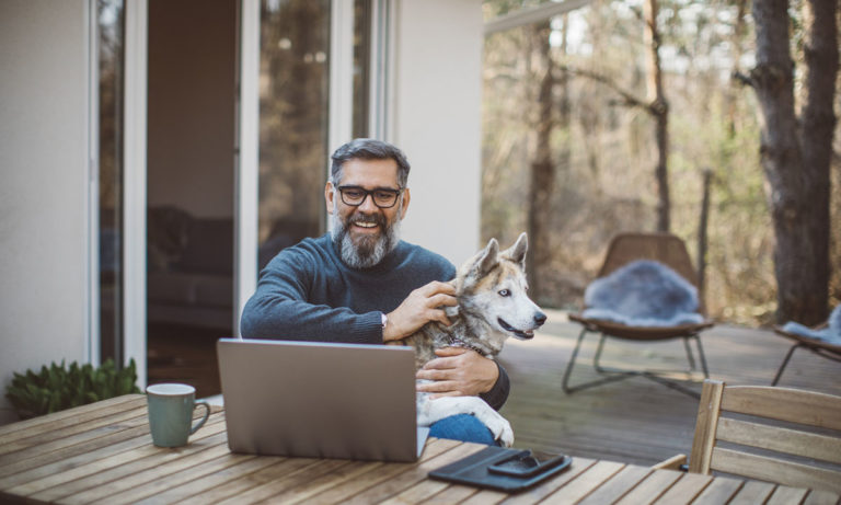 Engaged employee sitting on his deck working on his computer and petting his dog