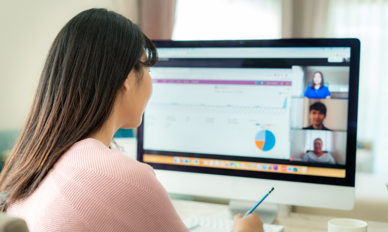 Woman sitting in front of her computer having a virtual meeting with three other remote workers