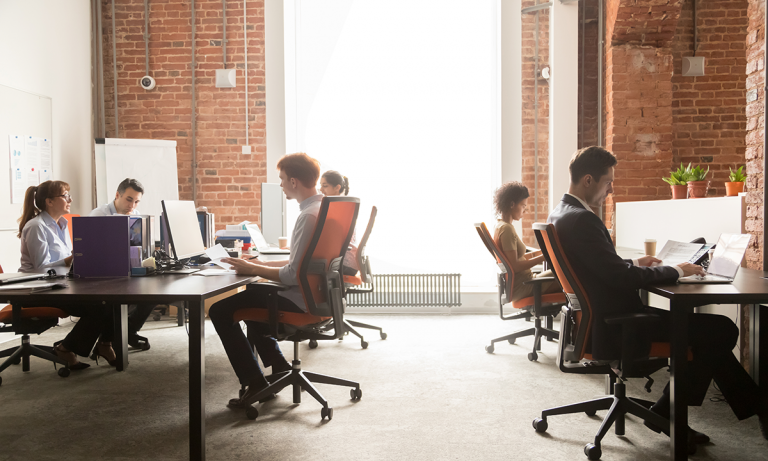 Employees sitting in an open concept office at their desks with laptops open