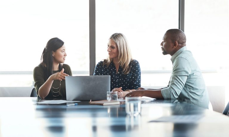 Two businesswomen and a businessman on a meeting talking in front of a laptop